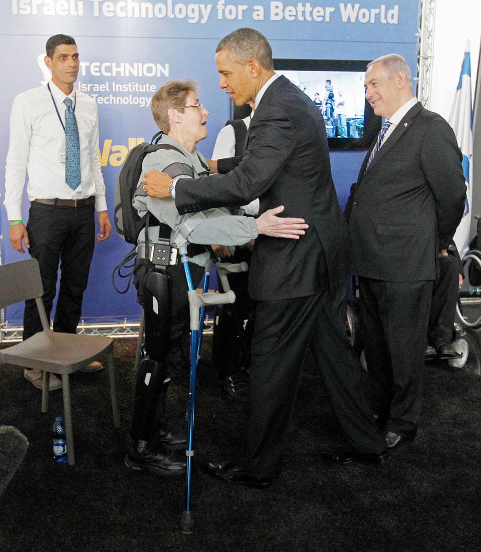 U.S. President Obama hugs U.S. Army Sergeant Hannigan as she wears an electronic leg technology named ReWalk during a tour of the technology expo in Jerusalem