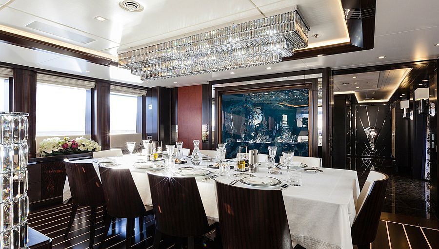 Expansive dining room inside luxury yacht with Macassar ebony dining table and stuning chandelier