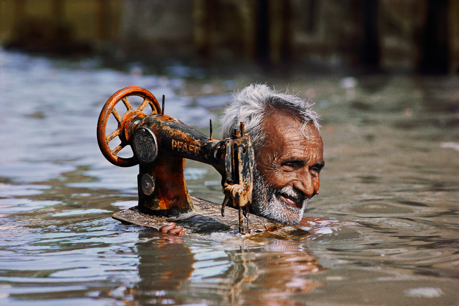 An old man carrying his sewing machine through neck-deep water in Porbandar, India. By Steve McCurry.