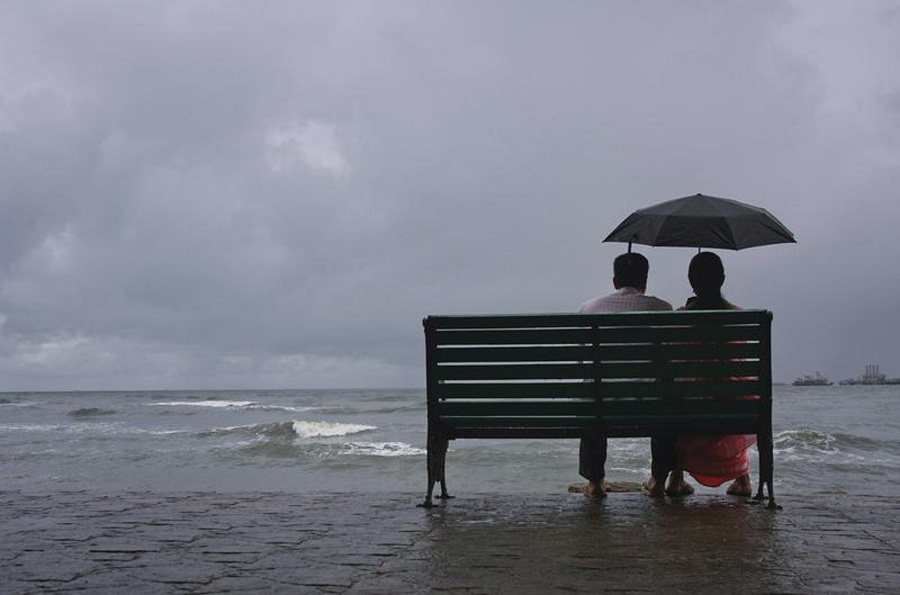 A couple rests on a seaside promenade during a rain shower in the south Indian city of Kochi. REUTERS/Sivaram V.