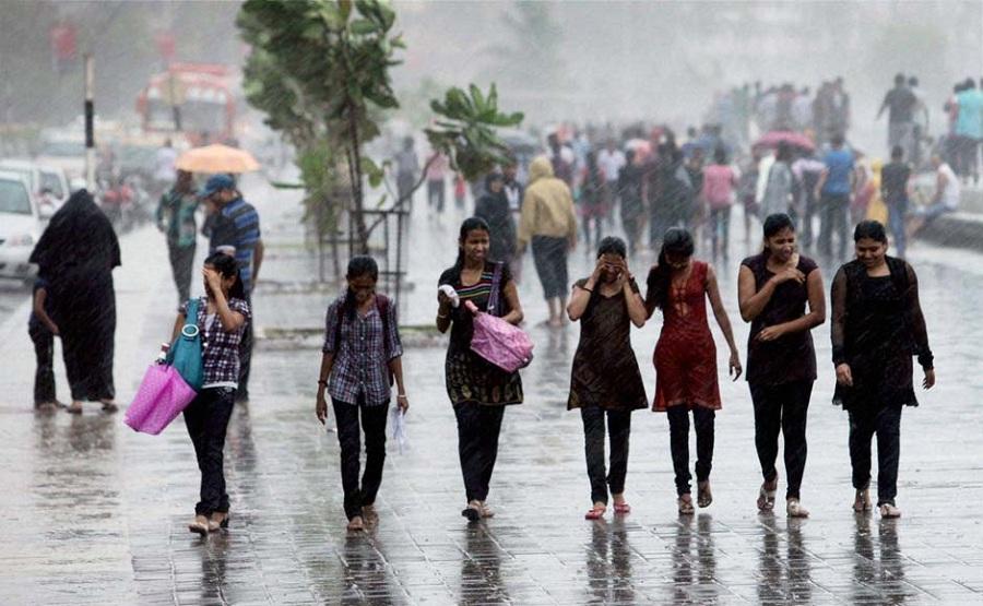 Girls enjoy a walk in the rain near Marine drive in Mumbai, India. PTI