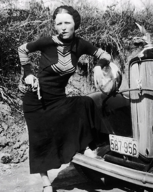 Bonnie Parker poses with a cigar and gun