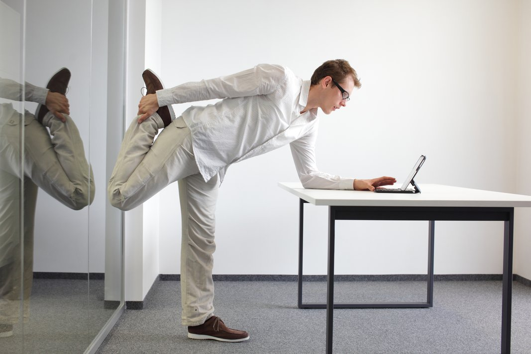 leg exercise durrng office work – standing man reading at tablet