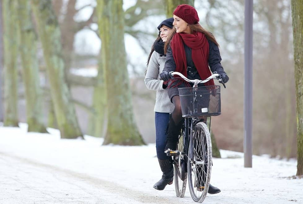 Cheerful Women Riding Bicycle Together
