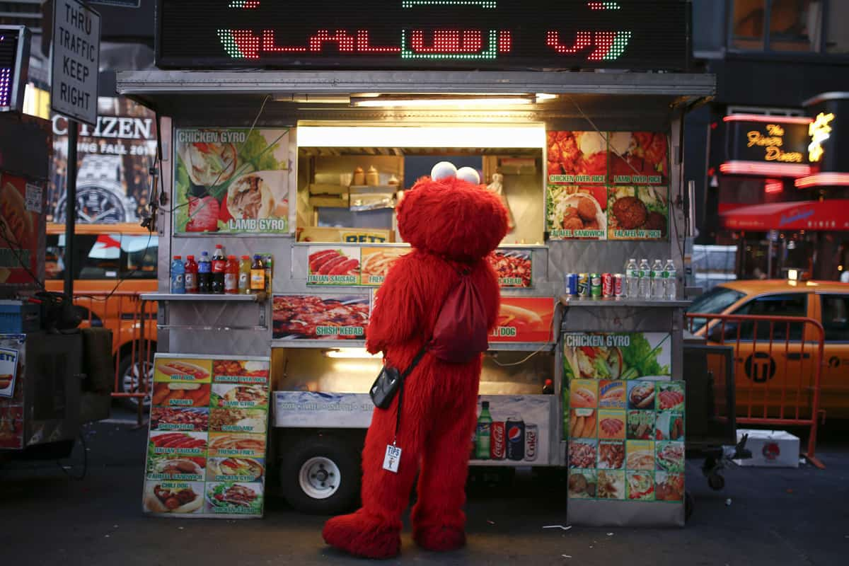 Jorge, an immigrant from Mexico, and dressed as the Sesame Street character Elmo, buys food from a street food cart in Times Square, New York