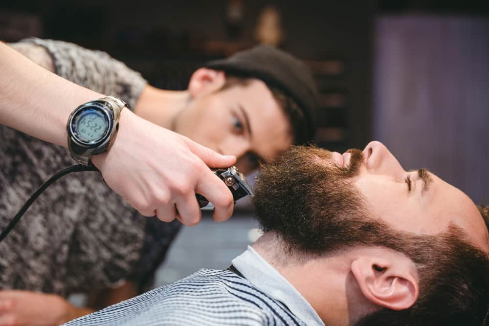 Attractive bearded man getting his beard shaved by modern barber in barber shop