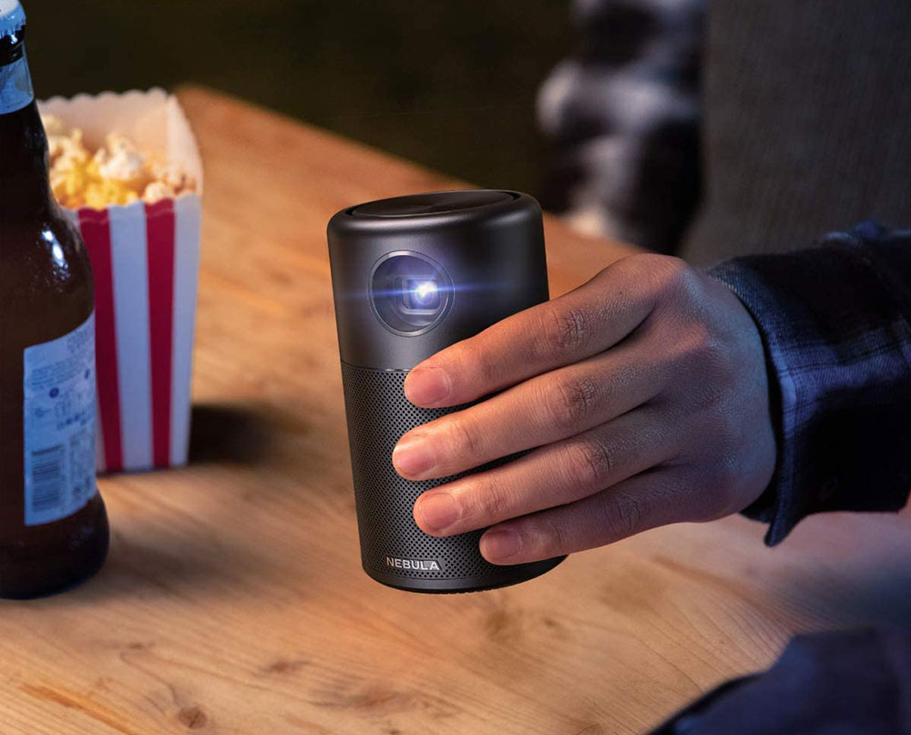 Anker Nebula Capsule Mini Projector next to popcorn and beer