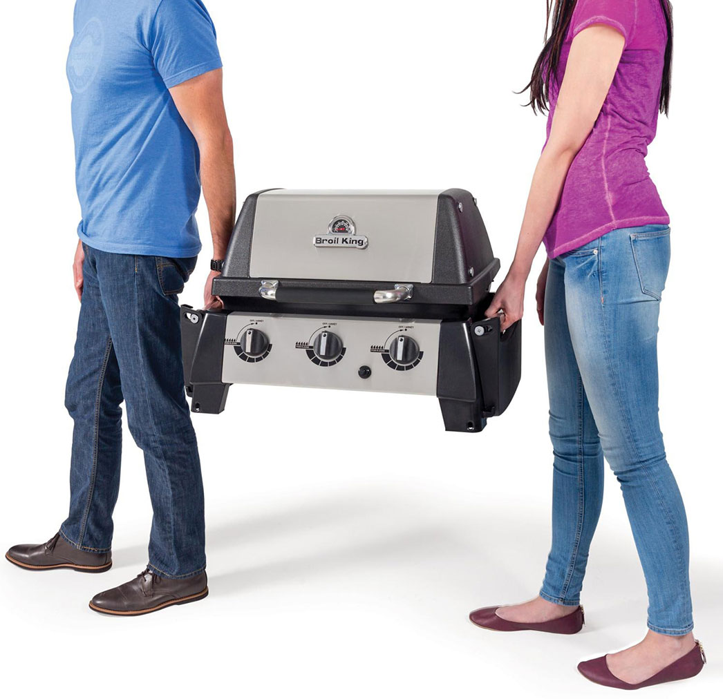 Two people carrying the Broil King Porta Chef 320