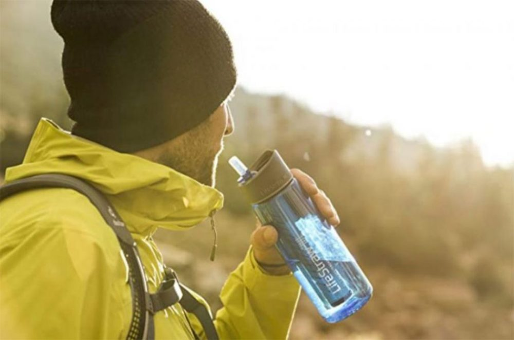 A hiker holding the LifeStraw Go