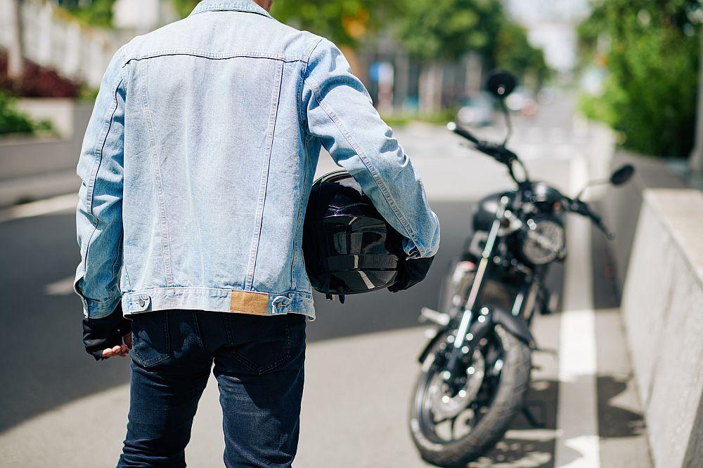 Man with motorcycle helmet and denim jacket